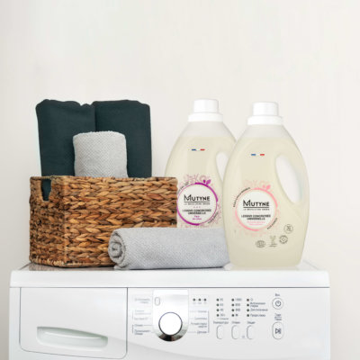 Cropped photo finished laundry process. Washing machine with sensor electronic display and set of towels on top standing isolated bright apartment light interior with copy space for advertised text